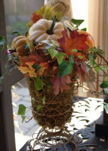 moss filled wire urns overflow with gourds, leaves and ivy.